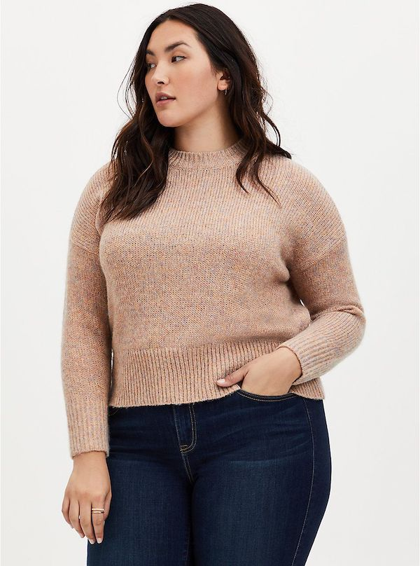 A model wearing a plus-size cropped sweater in tan.