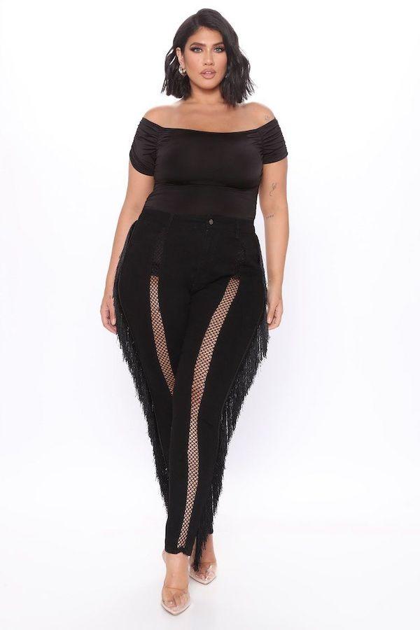 A model wearing plus-size fringe pants in black.
