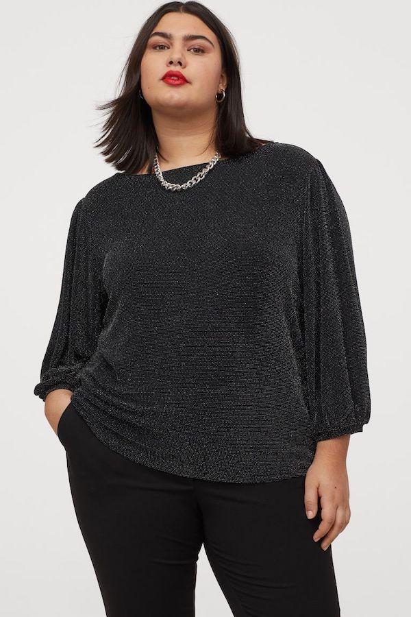 A model wearing a plus-size glitter top in black.