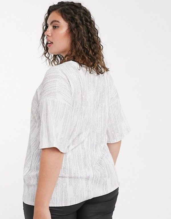 A model wearing a plus-size glitter top in white.