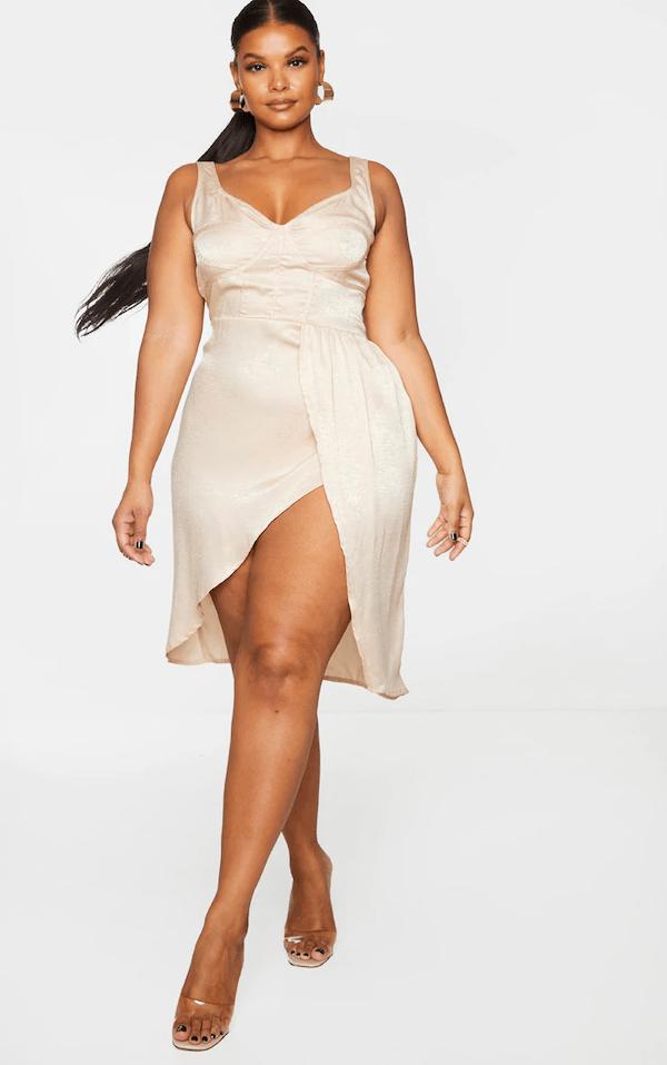 A model wearing a plus-size gold mini dress.