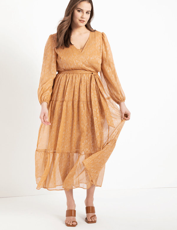 A model wearing a plus-size gold maxi dress.