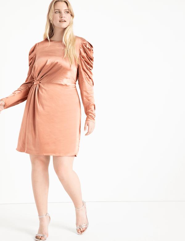 A model wearing a plus-size gold metallic mini dress.