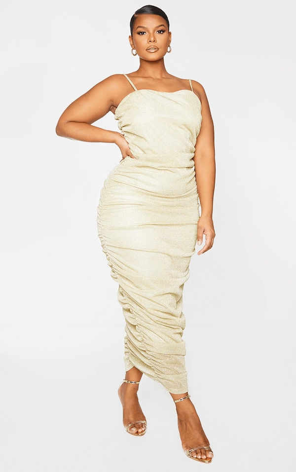 A model wearing a plus-size gold bodycon maxi dress.