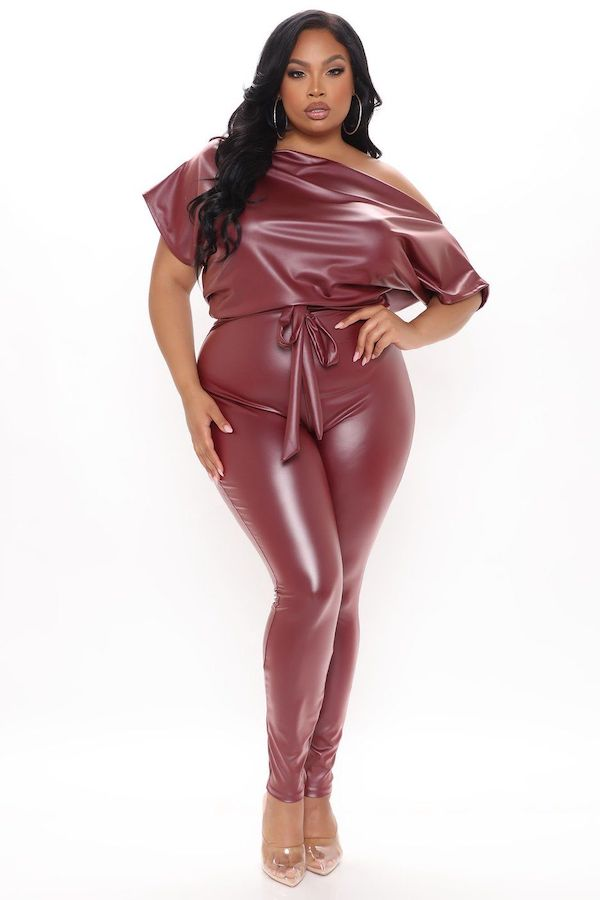 A model wearing a plus-size faux leather jumpsuit in rust.