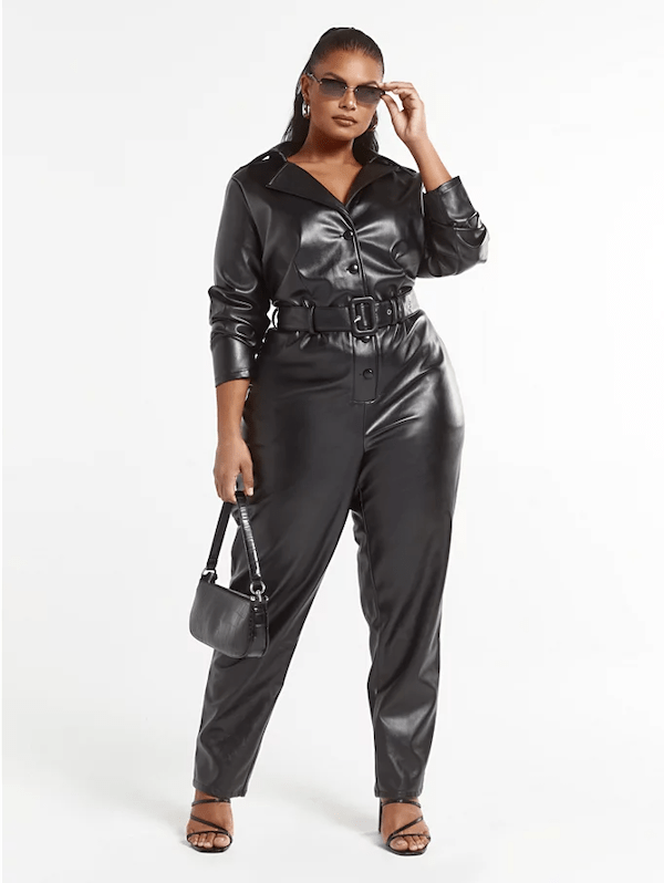 A model wearing a plus-size faux leather jumpsuit in black.