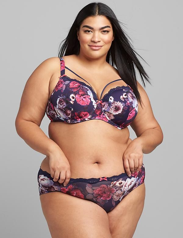 A model wearing a plus-size lingerie set in purple and pink floral.