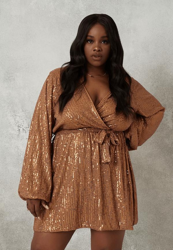 A model wearing a plus-size gold wrap dress.