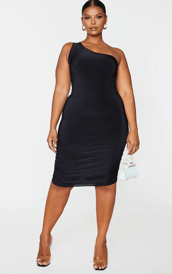 A model wearing a plus-size black mini dress.