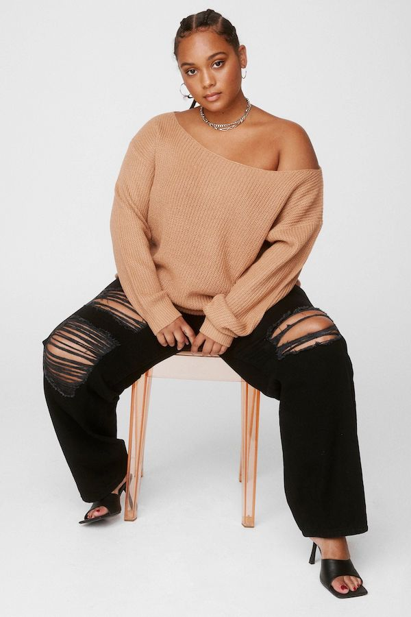 A model wearing a plus-size off-the-shoulder sweater in brown.