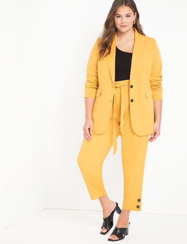 A model wearing a plus-size pant suit in yellow.
