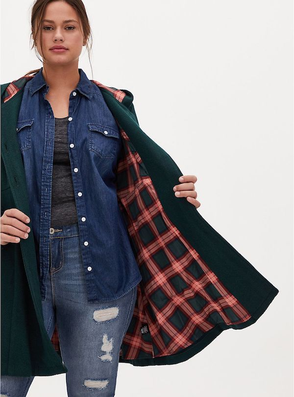 A model wearing a plus-size plaid coat in green and pink.