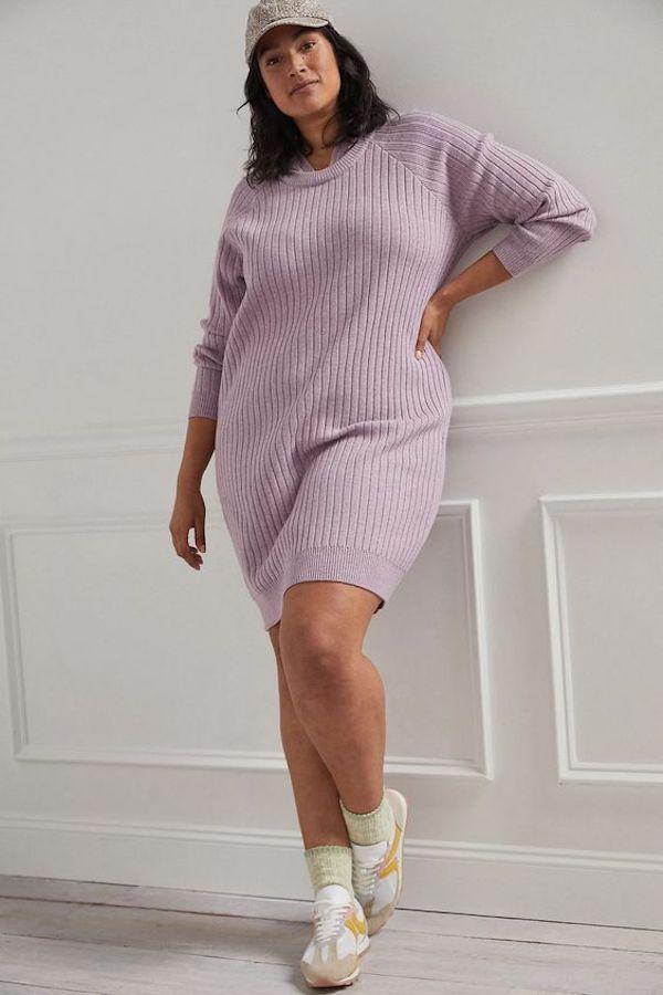 A model wearing a plus-size purple sweater dress.