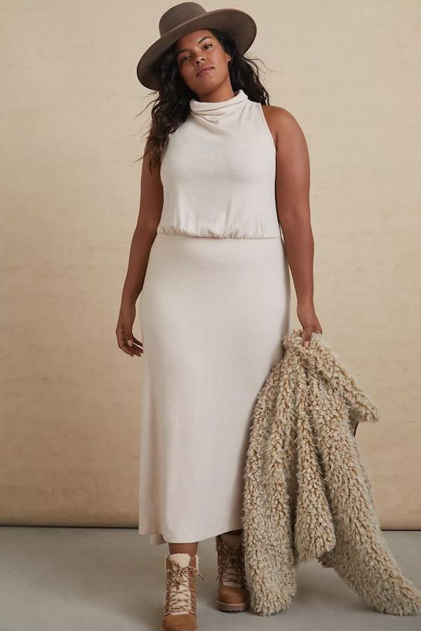 A model wearing a plus-size white sweater dress.