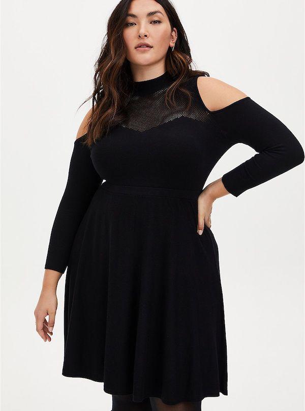 A model wearing a plus-size black sweater dress.