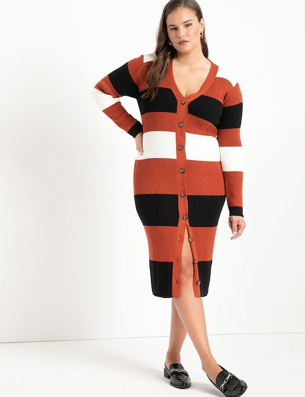 A model wearing a plus-size orange, black, and white stripe sweater dress.