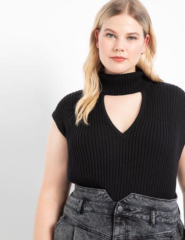 A model wearing a plus-size turtleneck sweater in black.