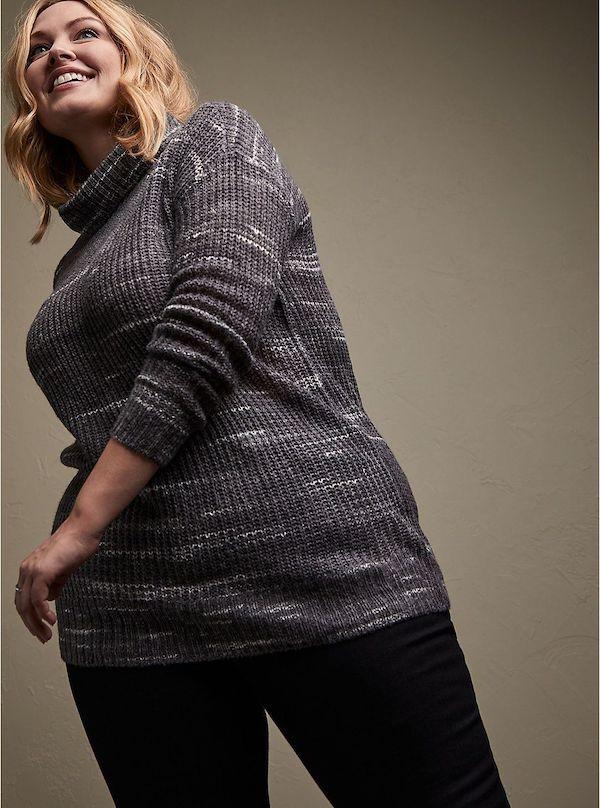 A model wearing a plus-size turtleneck sweater in dark gray.