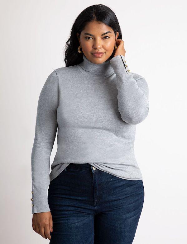 A model wearing a plus-size turtleneck sweater in gray.
