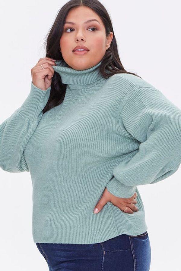 A model wearing a plus-size turtleneck sweater in light blue.