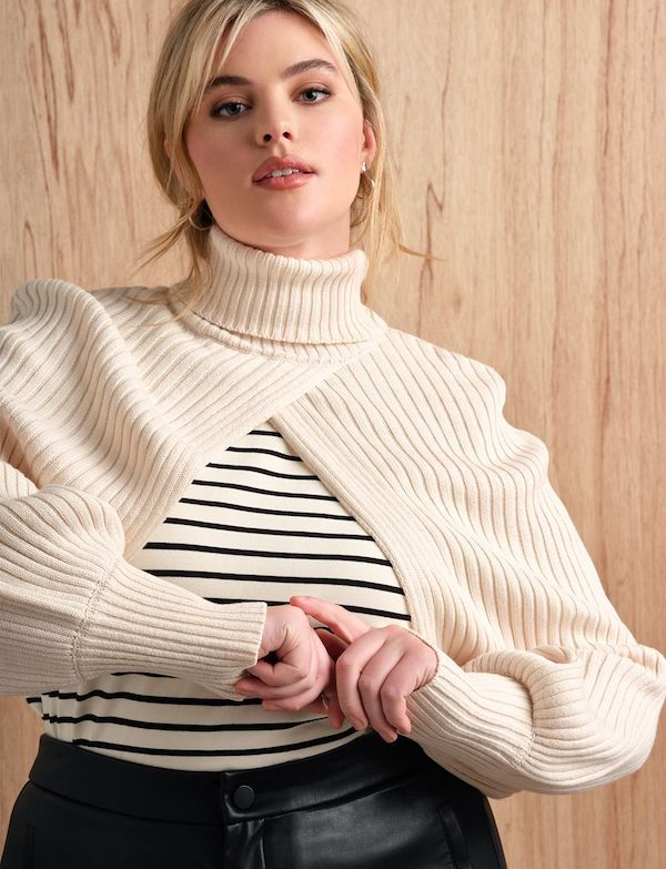 A model wearing a plus-size turtleneck sweater in cream.