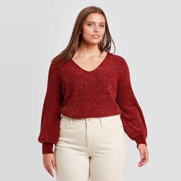 A model wearing a plus-size v-neck sweater in red.