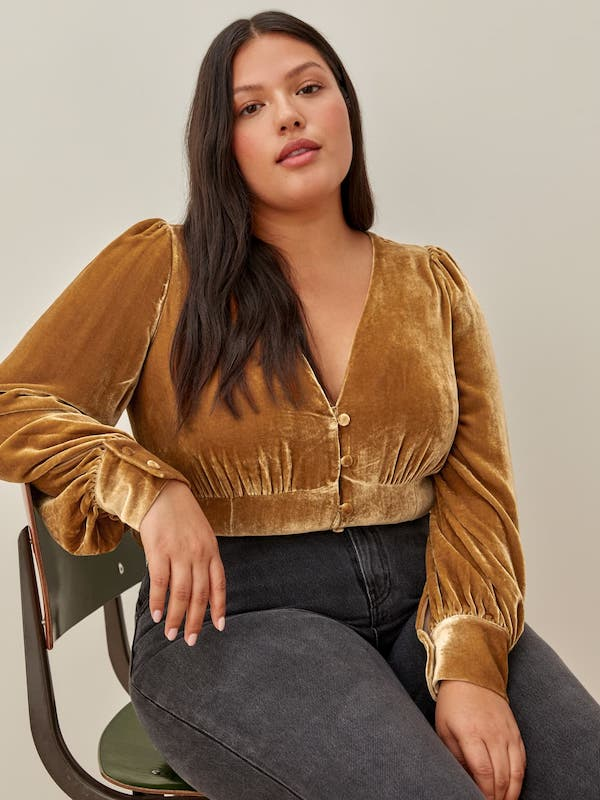 A model wearing a plus-size yellow velvet top.