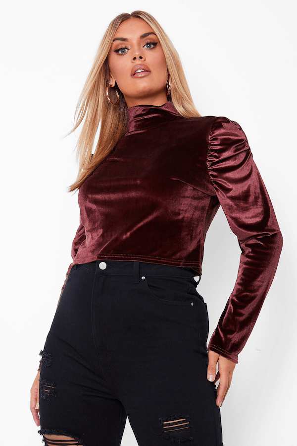 A model wearing a plus-size dark magenta velvet top.
