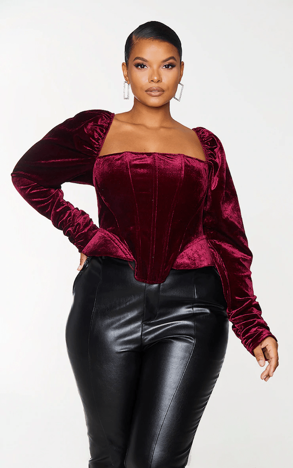 A model wearing a plus-size magenta velvet top.