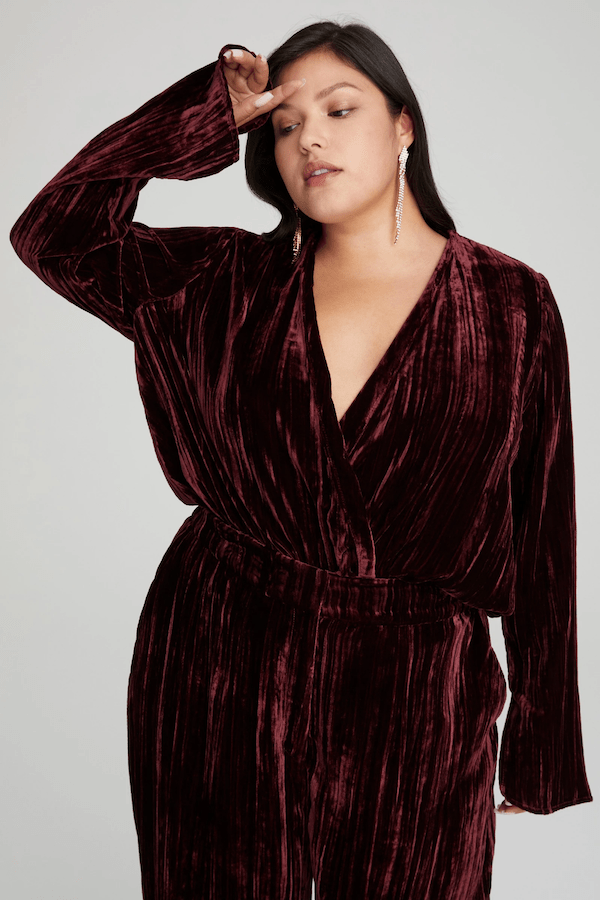 A model wearing a plus-size dark red velvet bodysuit.