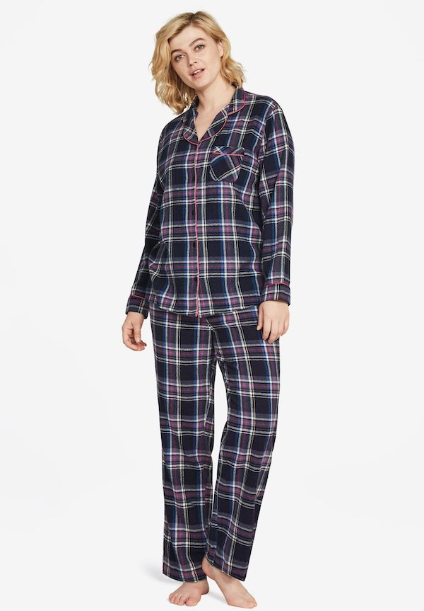 A model wearing plus-size flannel pajamas in dark blue and pink.