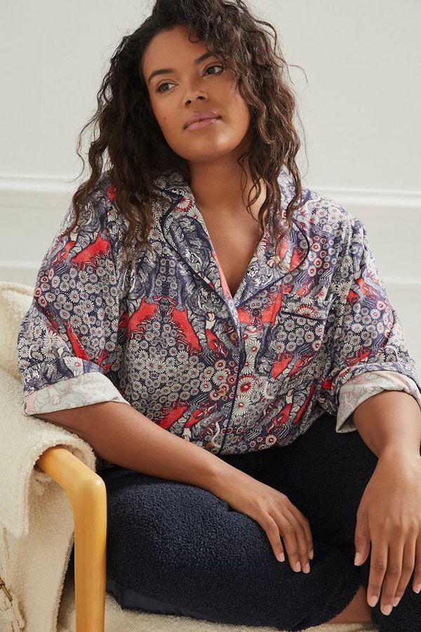 A model wearing plus-size flannel pajamas in a red and gray print.