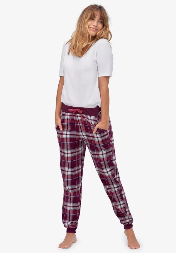 A model wearing plus-size flannel pajamas in red and white plaid.