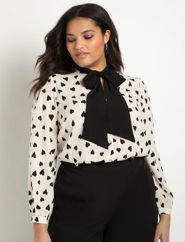 A model wearing a plus-size heart pattern top in black and white.