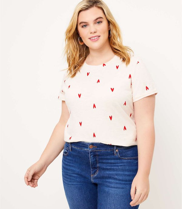 A model wearing a plus-size heart pattern top in white and red.