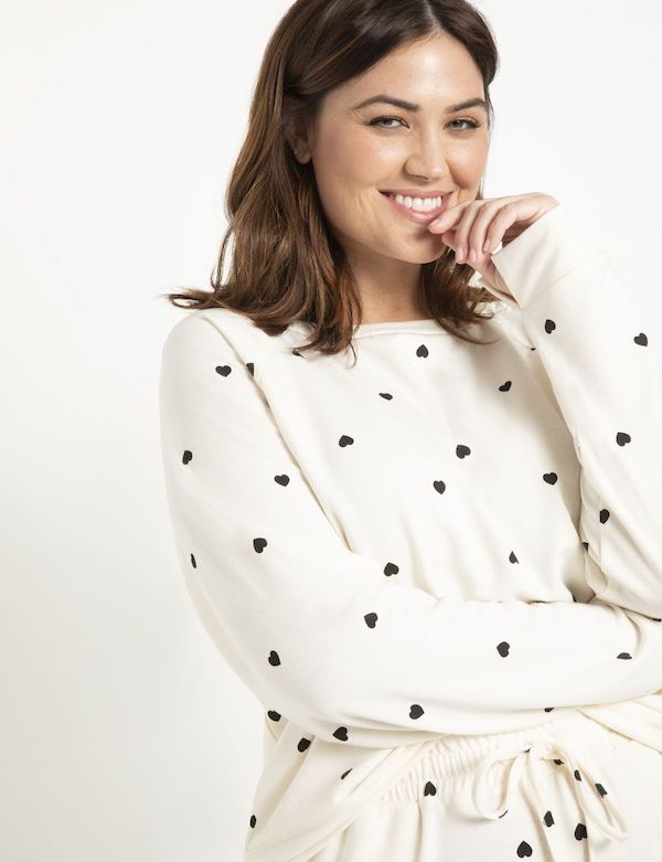 A model wearing a plus-size heart pattern top in white and black.