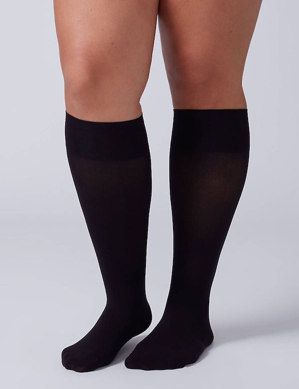A model wearing a pair of plus-size knee-high socks in black.