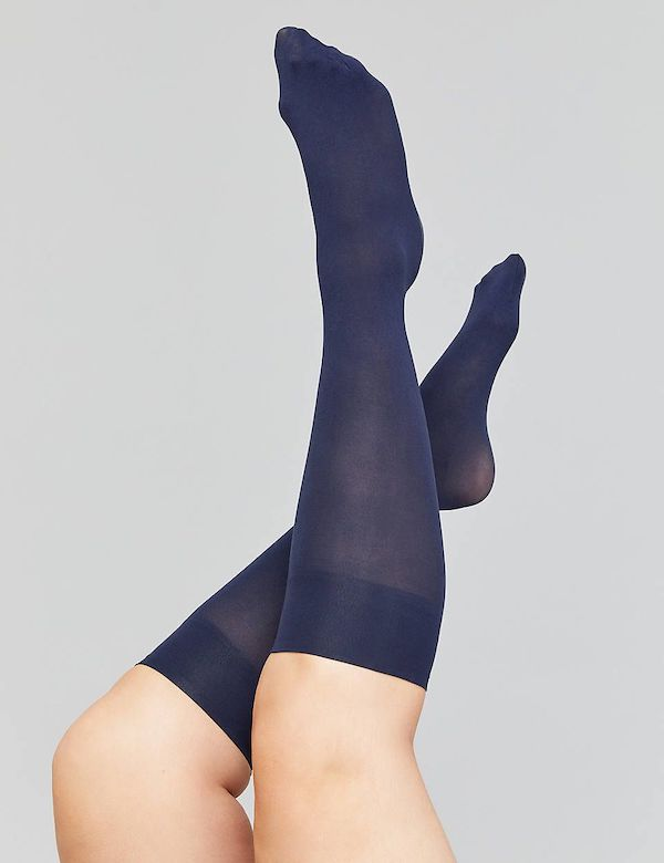 A model wearing a pair of plus-size knee-high socks in navy.
