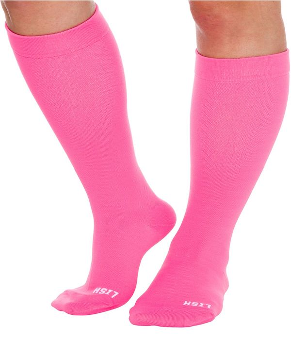 A model wearing a pair of plus-size knee-high socks in pink.