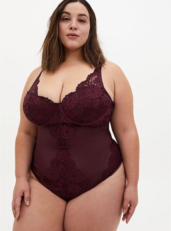 A model wearing a plus-size lace burgundy bodysuit.