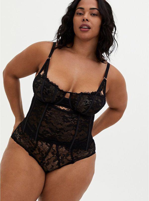 A model wearing a plus-size lingerie corset in black.