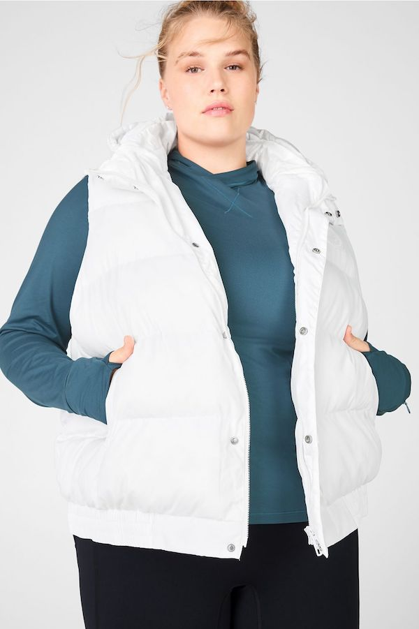 A model wearing a plus-size puffer vest in white.