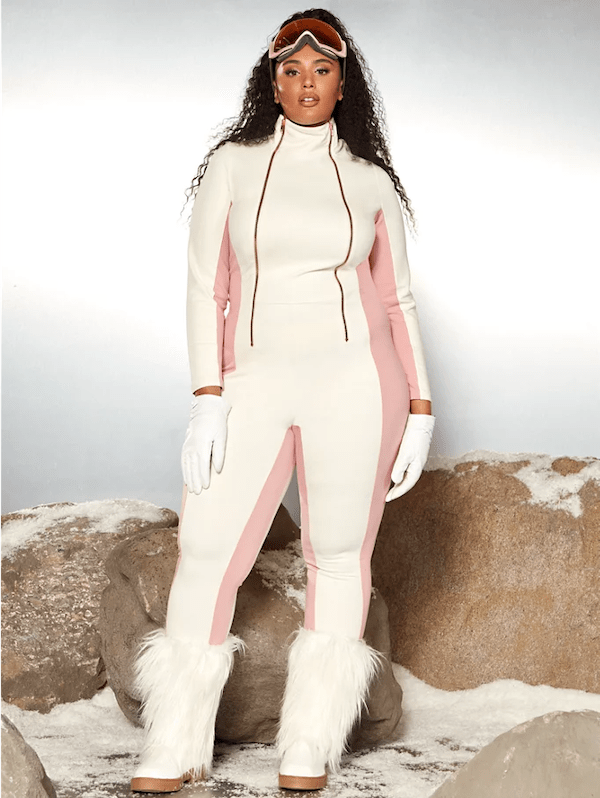 A model wearing a plus-size ski suit in white and pink.