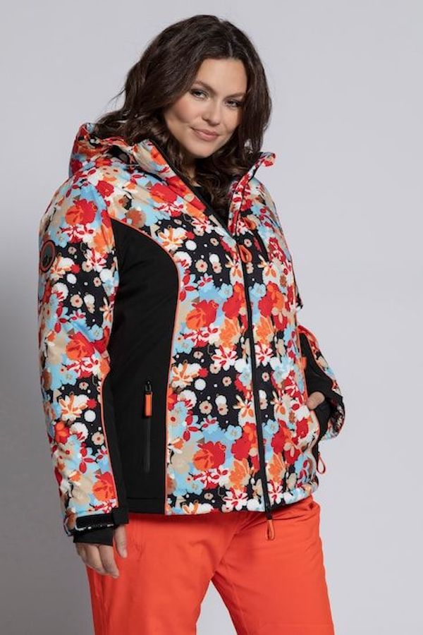 A model wearing a plus-size ski jacket in red, blue, and black print.