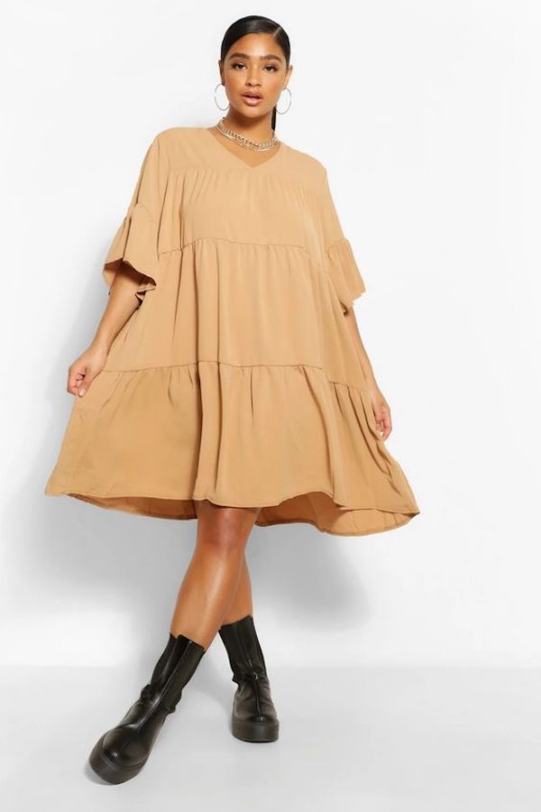A model wearing a plus-size smock dress in tan.