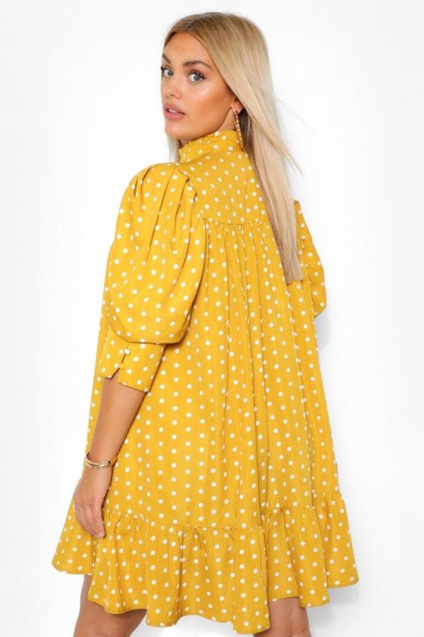 A model wearing a plus-size smock dress in yellow polka dot.