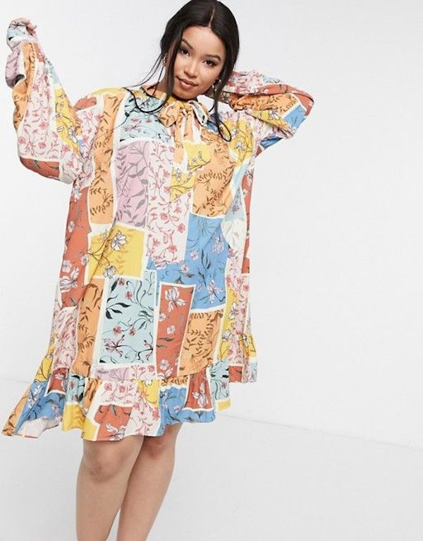 A model wearing a plus-size smock dress in colorful prints.