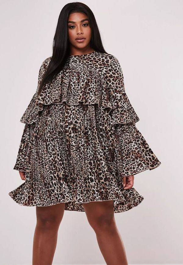 A model wearing a plus-size smock dress in animal print.