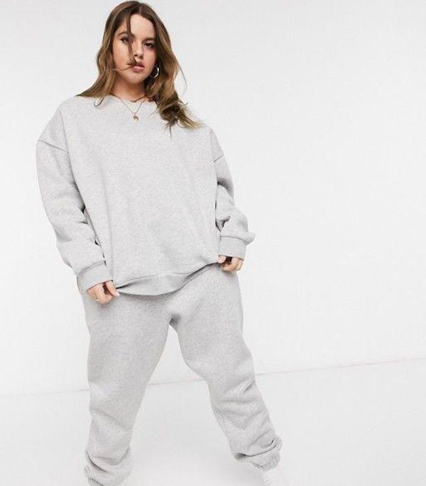 A model wearing a plus-size sweatsuit in gray.