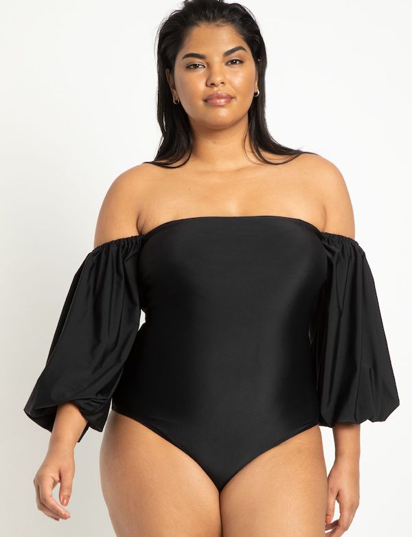 A model wearing a plus-size swimsuit with sleeves.